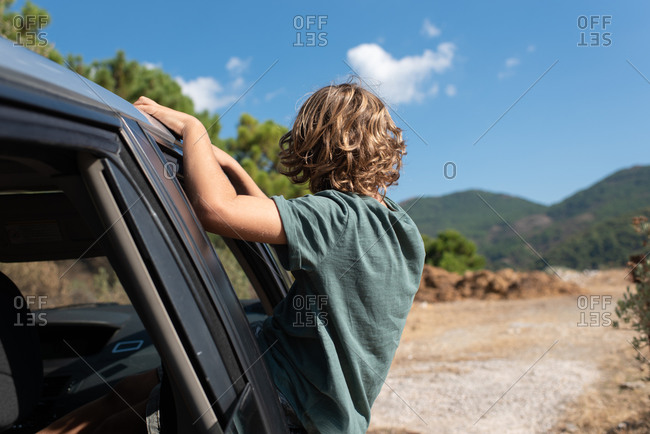 Back view of unrecognizable preteen boy with curly hair sitting in open window of automobile and looking away while enjoying summer adventure in mountainous land