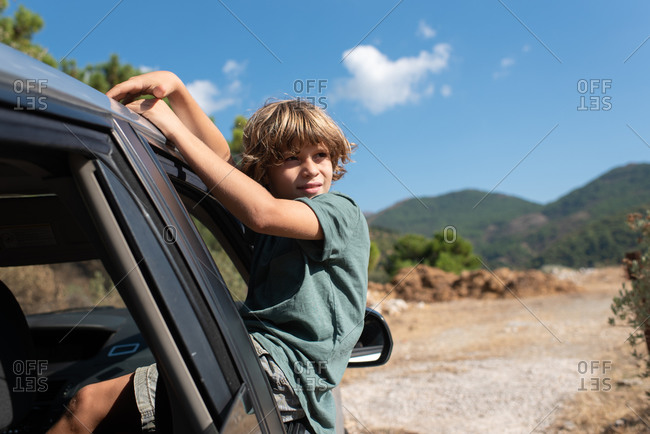 Side view of preteen boy with curly hair sitting in open window of automobile and looking away while enjoying summer adventure in mountainous land