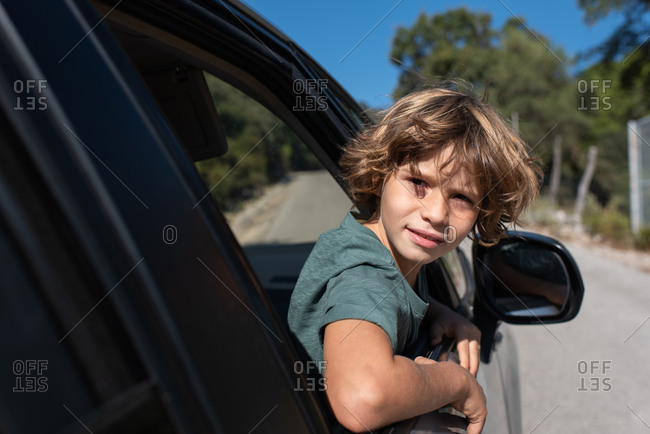 Side view of preteen boy with curly hair sitting in automobile looking out a window of while enjoying summer adventure in mountainous land