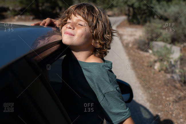 Side view of preteen boy with curly hair sitting in open window of automobile with eyes close while enjoying summer adventure in mountainous land