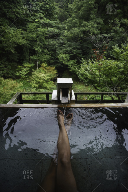 Legs and feet of caucasian female traveler enjoying a thermal waters bath in Japanese onsen, view from above