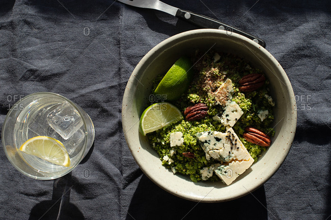 From above bowl with broccoli salad with couscous placed on dark fabric napkin