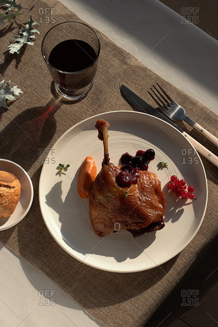 From above delicious fried duck confit on white ceramic plate placed on table of modern restaurant