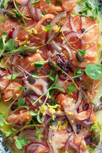 Closeup Tasty Salmon Sashimi Carpaccio Salad with Capers and Onion