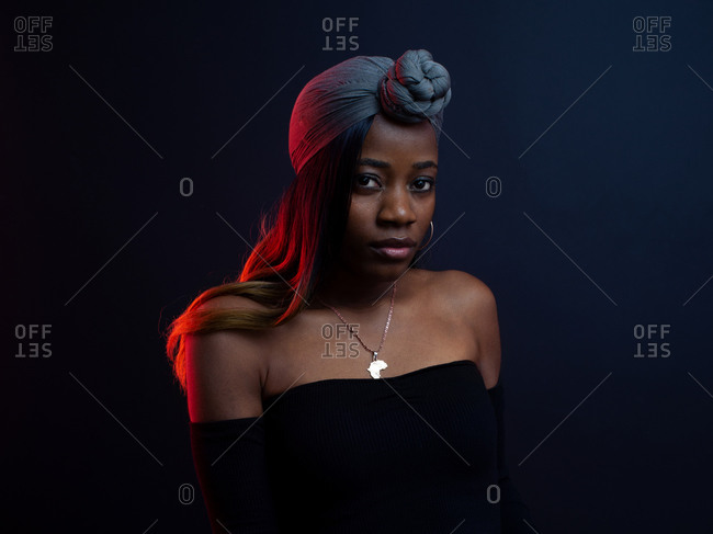 Attractive young African female model in stylish outfit with bare shoulders and traditional headwear standing against dark background looking at camera