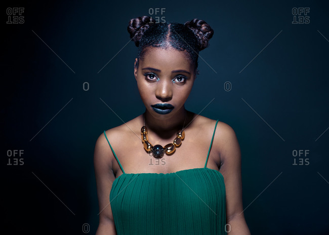 Fashionable young African American female model looking at camera while standing in dark studio