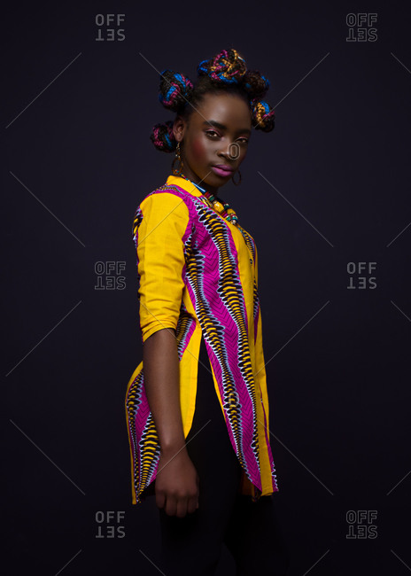 Side view of young African female model in bright colorful garment in traditional style looking at camera while standing against black background