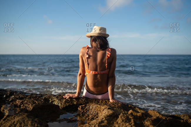 Back view of anonymous lady in swimwear and straw hat sunbathing on rocky beach of waving sea against blue sky during summer holidays