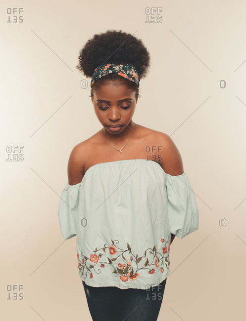 Young slim African American female model with Afro hair bun and headband wearing stylish blue crop top and jeans standing against beige background