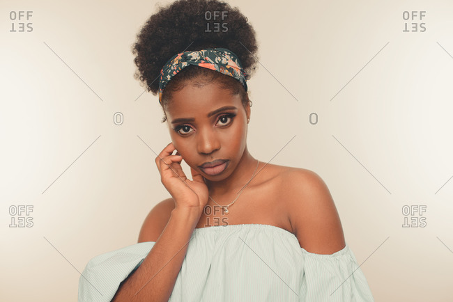 Young slim African American female model with Afro hair bun and headband wearing stylish blue crop top and jeans standing against beige background looking at camera