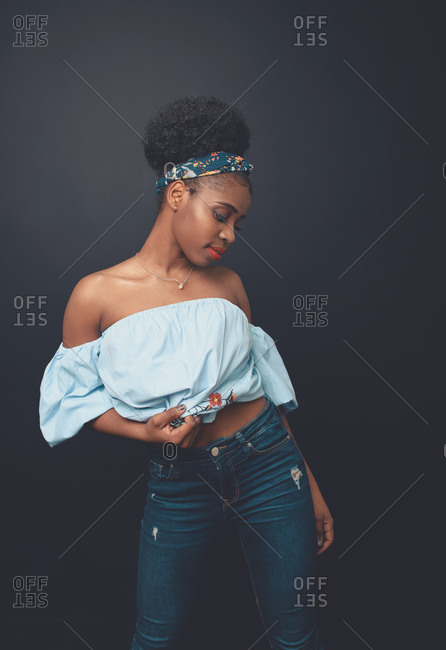 Young slim African American female model with Afro hair bun and headband wearing stylish blue crop top and jeans standing against black background