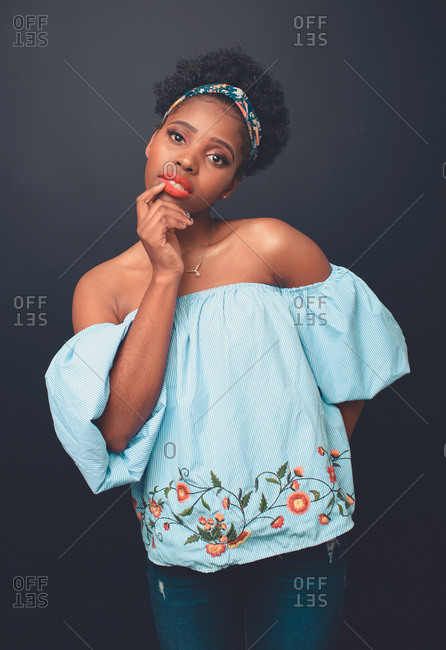 Young slim African American female model with Afro hair bun and headband wearing stylish blue crop top and jeans standing against black background looking at camera