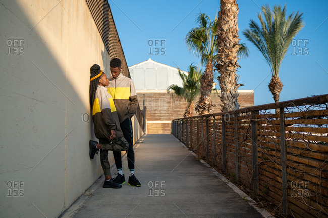 Full length of trendy young African American guy and lady in similar sportswear standing near wall in tropical park against cloudless blue sky after workout