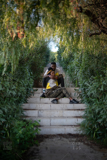 Full body of romantic young African American man and woman in similar outfits hugging sitting on stairs in green lush garden