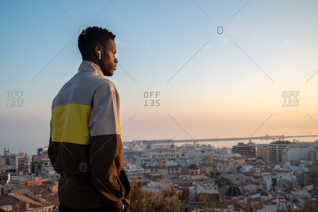 Side view of confident young ethnic male in trendy outfit and true wireless earphones admiring picturesque view of coastal city against cloudless sunset sky