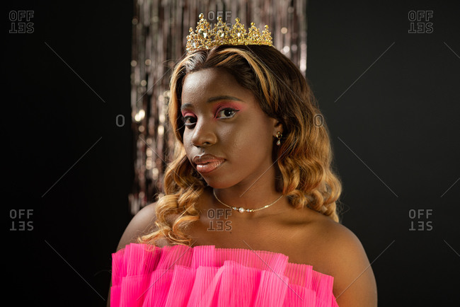 Self assured young black lady with long curly hair and makeup in pink fashionable dress and golden crown looking at camera during beauty contest