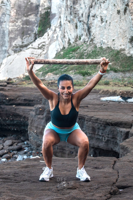 Delighted athletic female in sportswear doing squat exercise with wooden stick above head while training at seaside and looking at camera