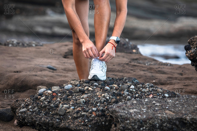Ethnic female athlete tying shoelaces on sneakers while sitting on seashore and preparing for workout