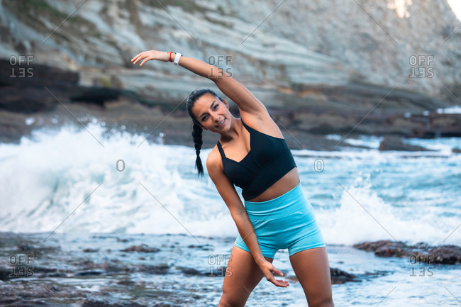 Positive female athlete warming up body and doing side bends while stretching arms before workout on seashore and looking at camera
