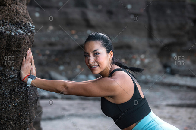 Side view of cheerful female with fit body leaning on rock on seashore and stretching body while warming up before workout and looking at camera
