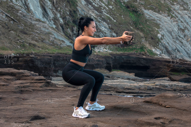 Side view of glad female athlete in sportswear doing squat exercise with rock while training in nature in summer
