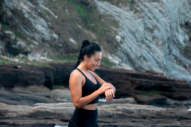 High angle of content sportswoman standing on seashore and checking pulse on modern smart watch during active workout in summer