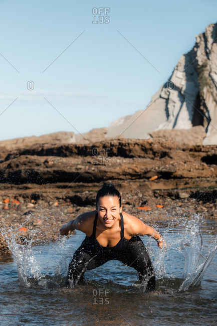 Positive female splashing water and looking at camera while standing in sea and having fun in summer