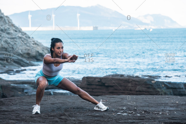 Peaceful female in sportswear doing yoga and balancing in Skandasana while practicing mindfulness in nature and looking at camera