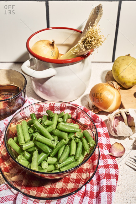 From above of fresh chopped green beans scattered on wooden cutting board placed on table near utensils and whole onions