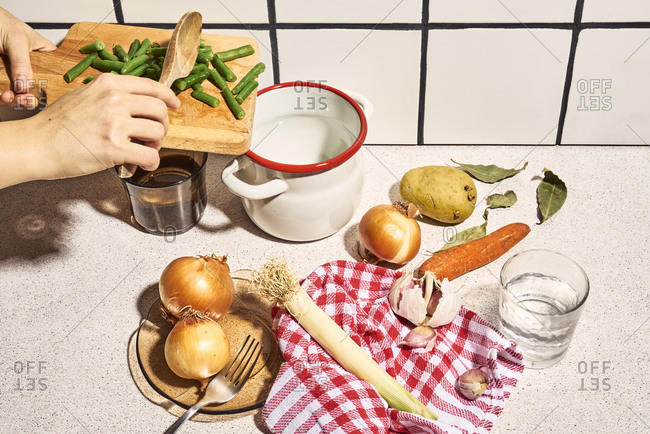From above of crop unrecognizable female adding chopped green beans into saucepan while preparing healthy soup with onions potato carrot and garlic in kitchen