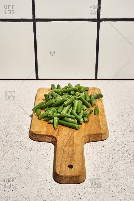 Pile of chopped green beans on wooden cutting board placed on table near glass of water in kitchen