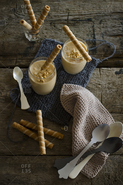 Appetizing nougat mousse dessert in glasses decorated with striped wafer rolls and nuts and served on wooden table in kitchen