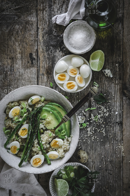 From above of delicious healthy quinoa salad with avocado eggs and asparagus placed on wooden table with ingredients bowls in kitchen