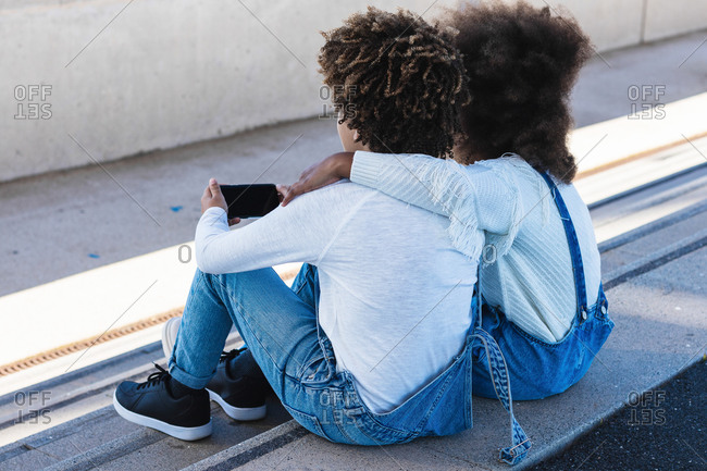 Back view of unrecognizable curly haired African American teen siblings in similar denim clothes hugging and browsing smartphone while sitting together on street