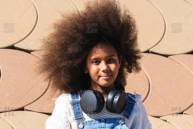 Teen black hipster girl with afro hairstyle listening to music through wireless headphones and looking at camera while resting on street