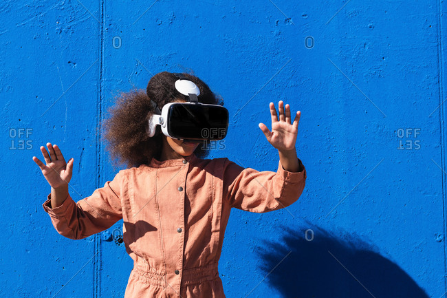 Unrecognizable African American girl in trendy suit and VR headset touching air while exploring virtual world against blue wall on street