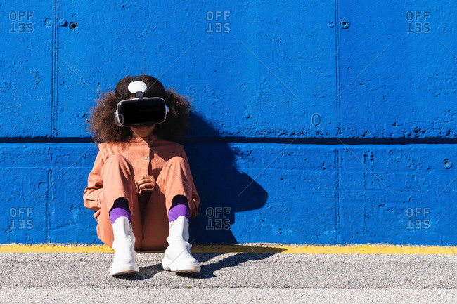 Unrecognizable African American girl in trendy suit and VR headset exploring virtual world while sitting against blue wall on the street