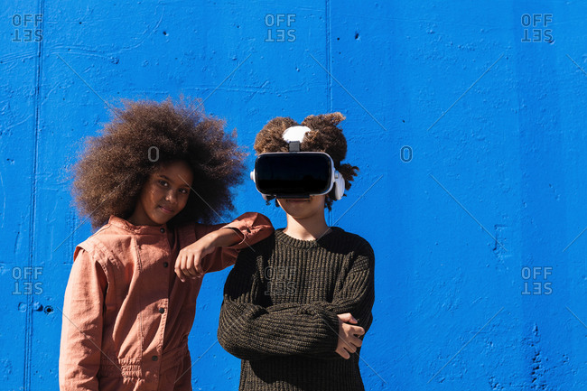Positive teen black girl with curly hair standing near unrecognizable friend wearing VR headset while spending time together and experiencing virtual world against blue wall on street