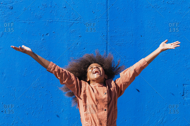 Overjoyed African American female teenager with curly hair raising arms and laughing happily while enjoying summer holidays against blue wall