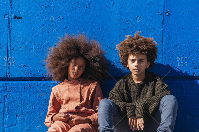 African American teen hipster friends with Afro hairstyle sitting against bright blue wall while spending free time together and resting on street