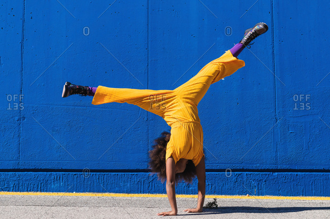 Full body of African American teen girl in bright yellow jumpsuit performing handstand against blue wall on street