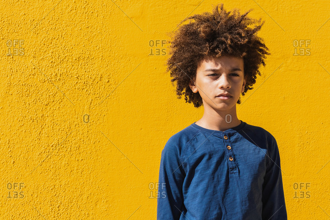 Thoughtful teenager boy with Afro curly hair standing looking at camera against yellow background