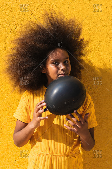 African American teen girl with curly hairstyle holding black balloon while standing against yellow background looking away