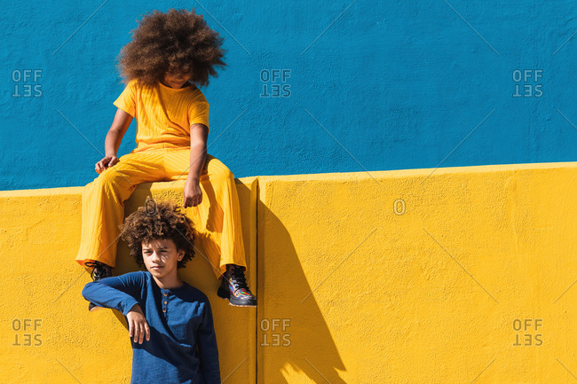Teen African American girl and boy with afro hairstyle wearing colorful clothes resting together against blue and yellow wall in sunny day on street