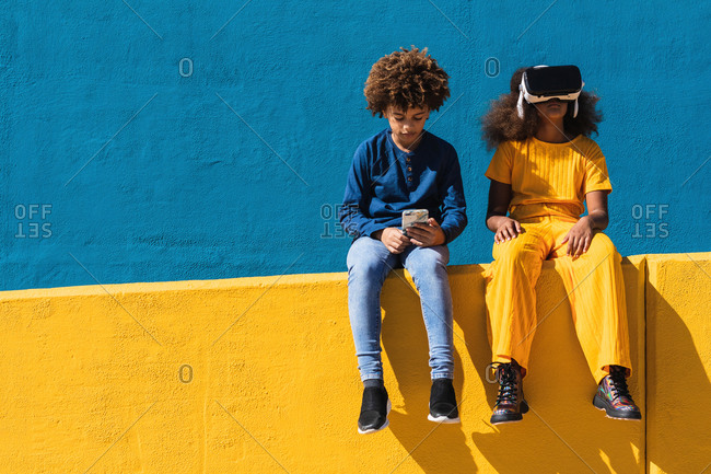 Low angle of African American teen boy with smartphone and girl in VR headset sitting together on colorful wall on street