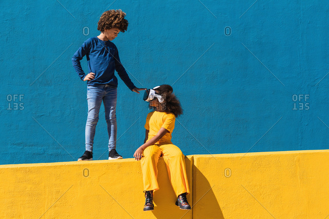 Low angle full body of African American boy communicating with girlfriend wearing VR headset while playing virtual game near colorful wall