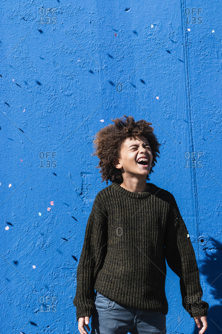Happy curly haired African American male teenager in casual clothes laughing brightly while having fun against blue wall with falling confetti