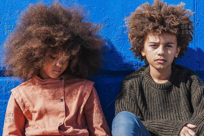 African American teen siblings with curly hairstyle in casual clothes sitting together against blue wall in sunlight