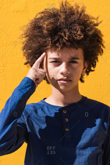 Thoughtful teenager boy with Afro curly hair touching temple and looking at camera pensively against yellow background