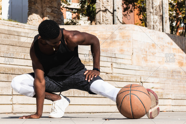 Fit African American male basketball player warming up legs and doing side lunges while preparing for training on sports ground in summer